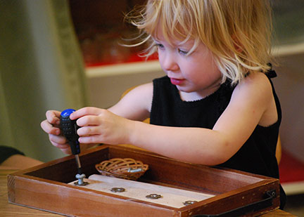 A child works with screws and a screwdriver in the primary program.
